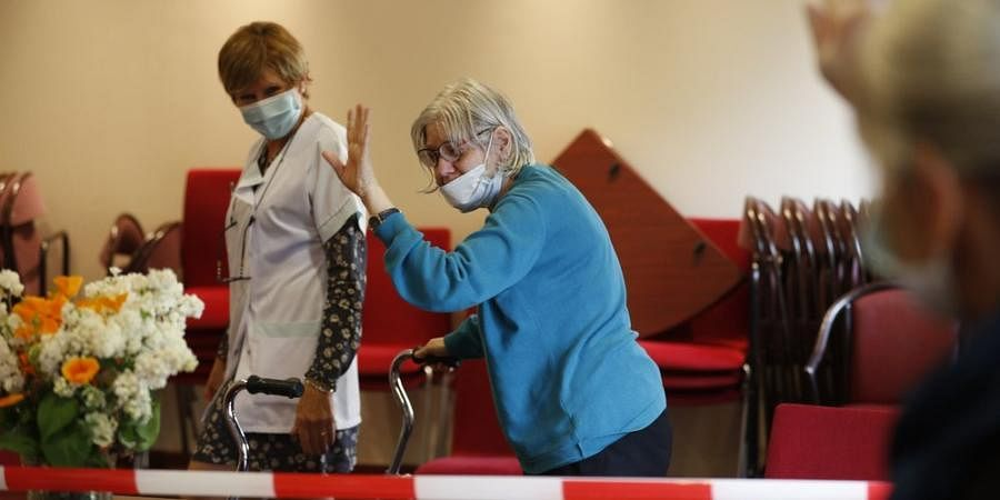 Monique Hernent, 65, waves goodbye after her sister's visit to her care home in eastern France.