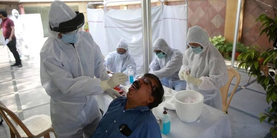 A doctor takes a swab sample of a journalist at a COVID-19 coronavirus testing camp for journalists in New Delhi on Wednesday.