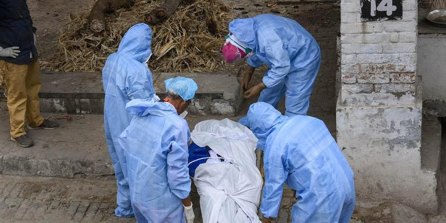 Medics prepare to cremate a COVID-19 patient during the nationwide lockdown to curb the spread of coronavirus, in Jalandhar