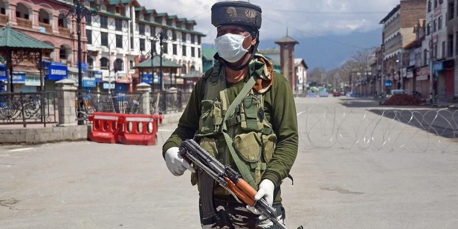 A CRPF personnel wearing a facemask stands guard during a nationwide lockdown as a preventive measure against the COVID-19 coronavirus, in Srinagar