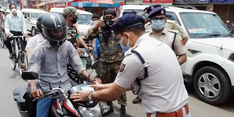 Police officials stop the commuters and request them to stay at home during the nationwide COVID-19 lockdown in Birbhum