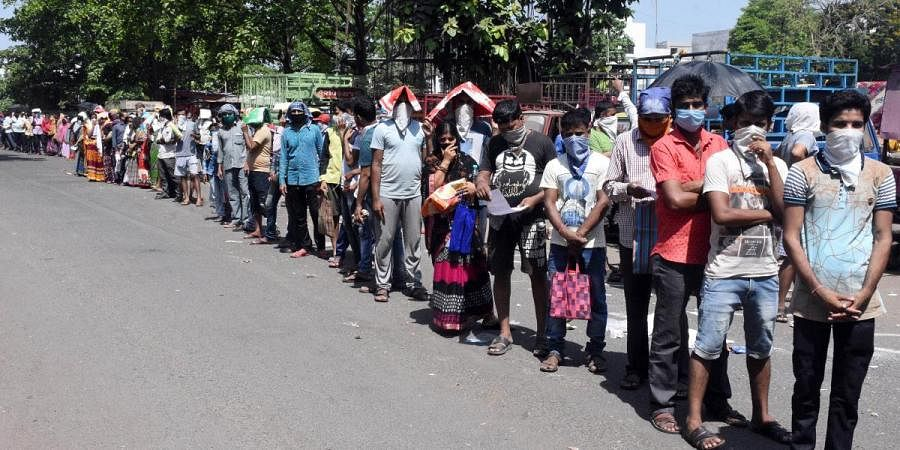 People stand in a queue to get the foodgrains which are being distributed at a PDS center during the nationwide COVID-19 lockdown in Surat
