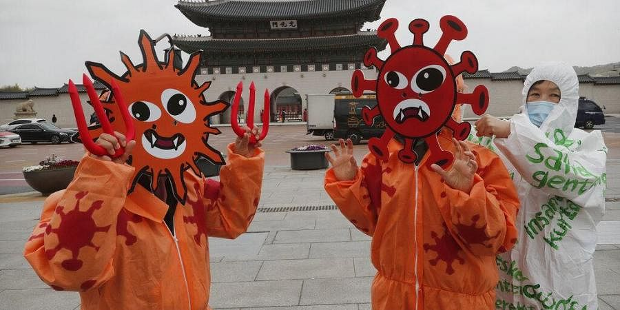 Members of the Environmental Health Citizens' Association of Korea wearing masks representing the viruses perform during an event to celebrate the 50th anniversary of Earth Day at Gwanghwamun Square in Seoul, South Korea, Wednesday, April 22, 2020.