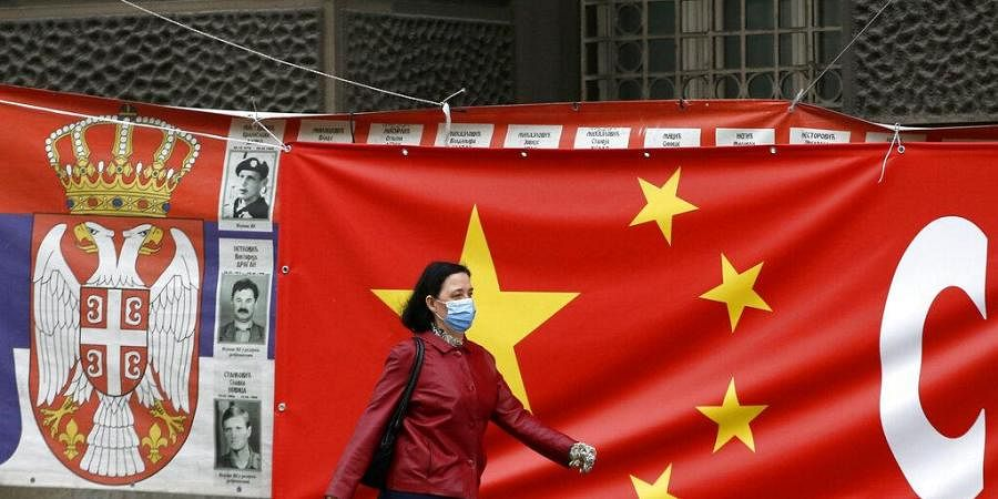 In this April 13, 2020, file photo, a woman wearing a face mask walks by a Chinese flag placed on a street prior a curfew set up to limit the spread of the new coronavirus in Belgrade, Serbia.