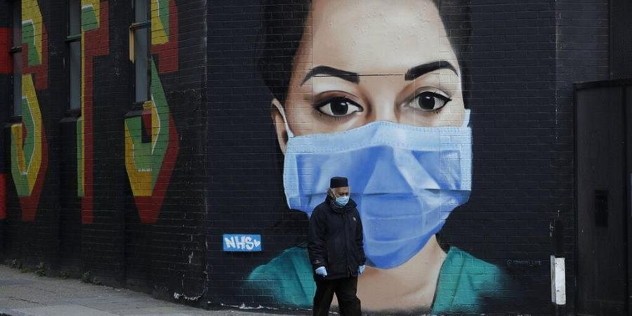 A man wearing a face mask and gloves to protect from coronavirus walks past a recently painted mural by professional street artist David Speed and the Graffiti Life collective to show appreciation for the people who work in the NHS in London.