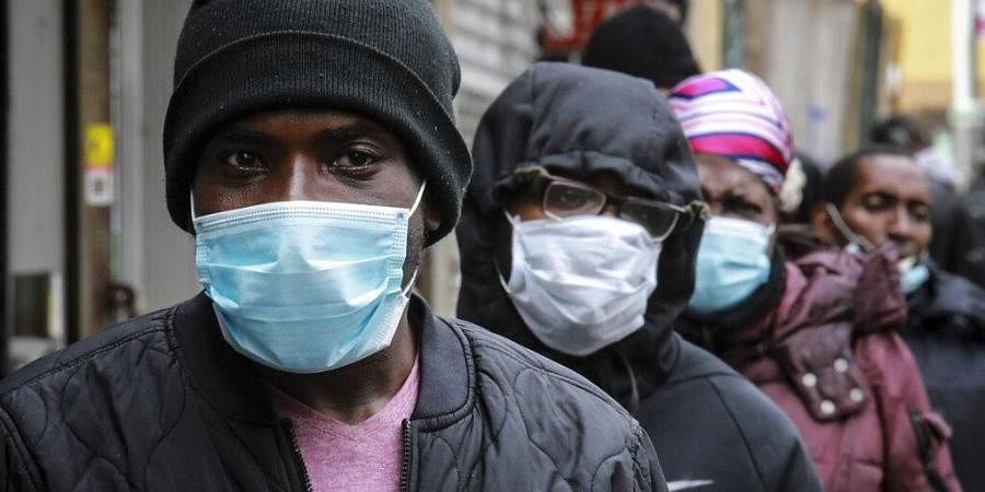 People wait for a distribution of masks and food from the Rev. Al Sharpton in the Harlem neighborhood of New York, after a new state mandate was issued requiring residents to wear face coverings in public due to the COVID-19 coronavirus, Saturday, April 18, 2020.