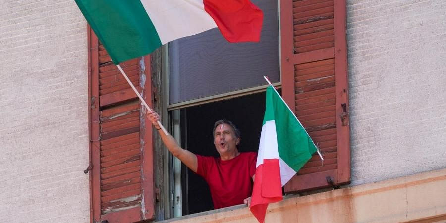 A man waves the Italian flag as he chants from his window on the occasion of the 75th anniversary of Italy's Liberation Day, in Rome