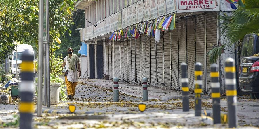 A woman walks past closed shops at Janpath market during a nationwide lockdown in the wake of coronavirus pandemic in New Delhi Tuesday April 14 2020.