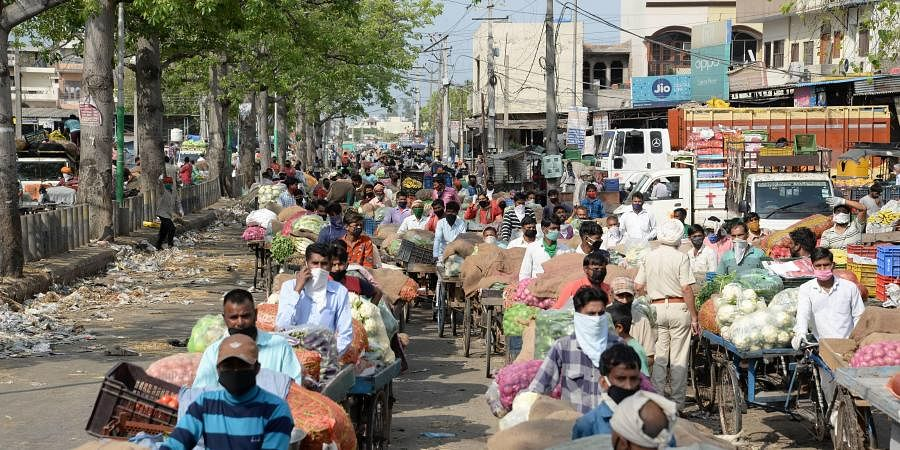 Vendors selling vegetbales wait to obtain a pass to enter a market during the nationwide lockdown to curb the spread of coronavirus in Jalandhar Saturday April 25 2020.