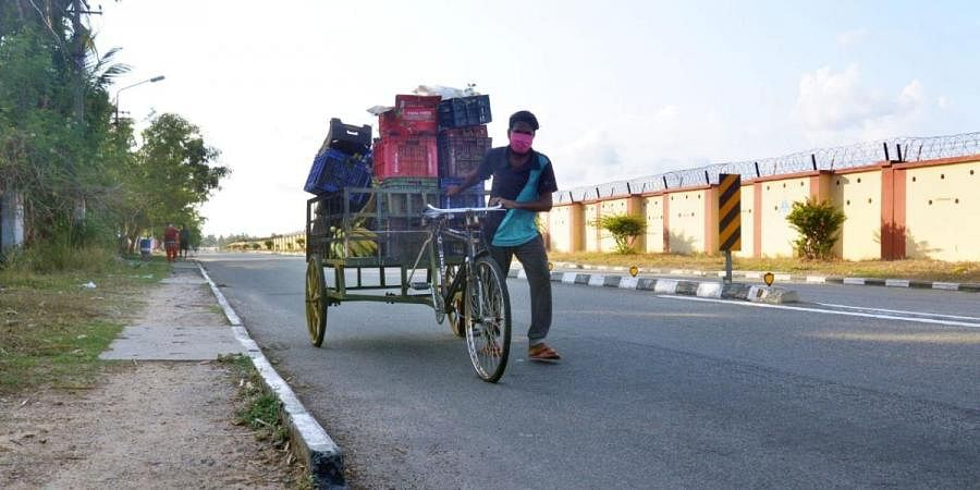 A worker carrying essential items in a bicycle trolley for supplying to the Air Force camp near the domestic airport at Thiruvananthapuram