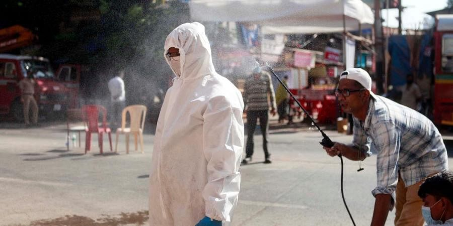 A BEST worker is being disinfectant by a man before going in a red zone area near Worli in Mumbai