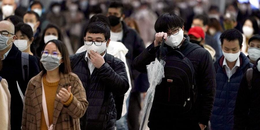 n this April 20, 2020, file photo, a station passageway is crowded with face mask wearing commuters during a rush hour, in Tokyo.