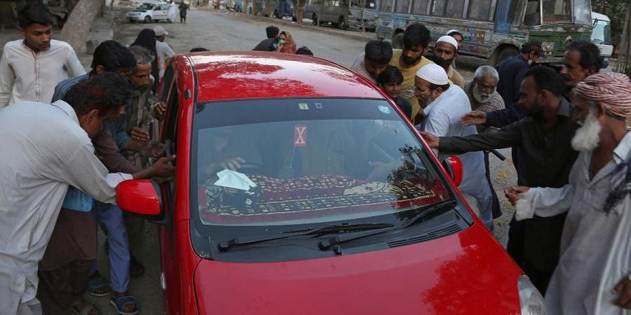People surround a car to receive free food being distributed by a family for breaking their fast, on the second day of Ramadan in Karachi