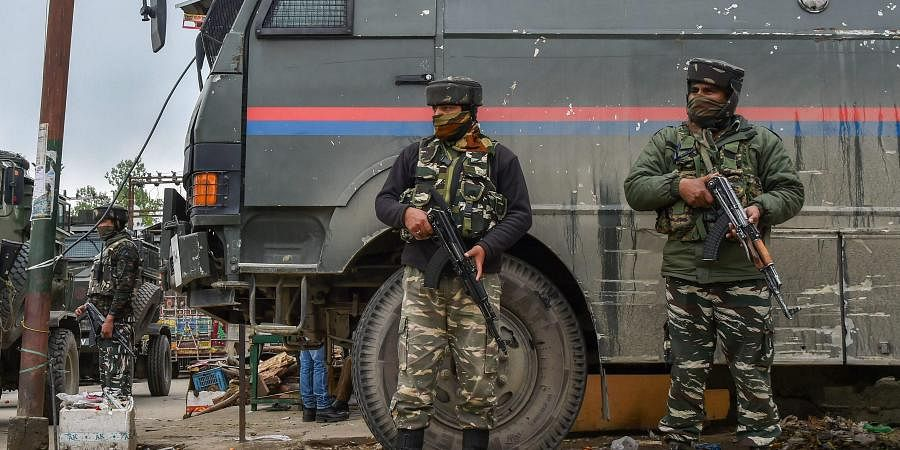 Security personnel stand guard during an encounter with the militants at Khudwani in Kulgam district of south Kashmir