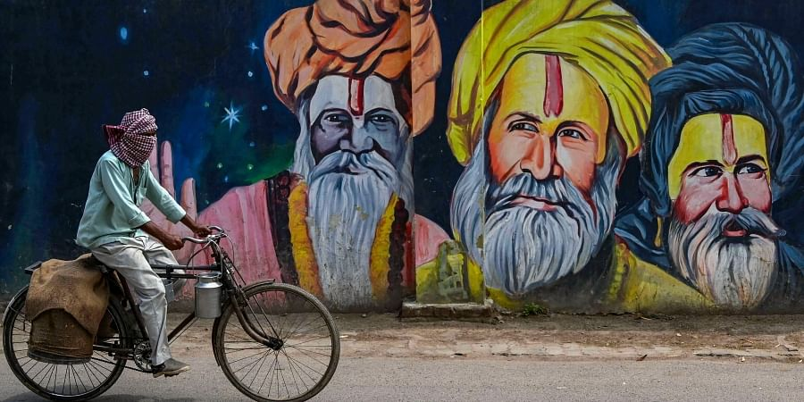 A milkman cycles past a mural depicting sadhus during ongoing COVID-19 lockdown in Prayagraj Sunday April 26 2020.