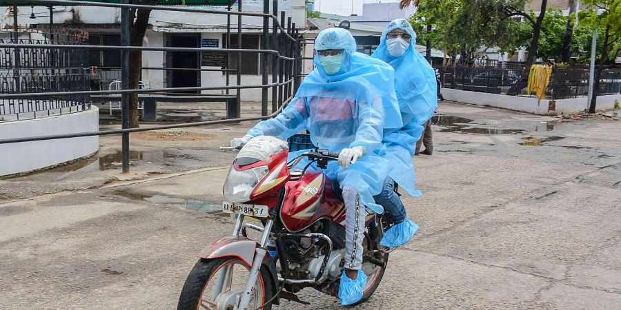 Medics wearing protective suits are seen riding a bike during a nationwide lockdown to curb the spread of coronavirus in Patna Sunday April 26 2020.