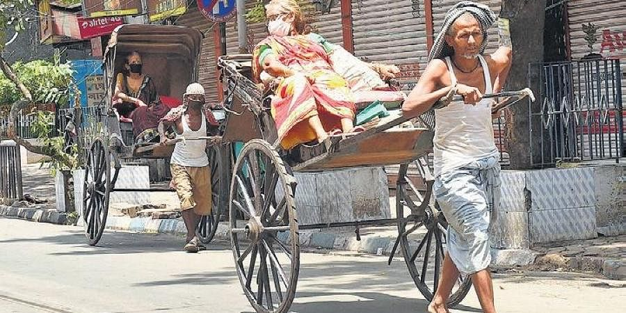 Passengers wear face masks on hand-pulled rickshaws in Kolkata