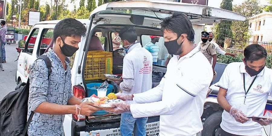 The workers of an NGO distribute free food to the needy near the JBS bus station in Hyderabad  on Thursday