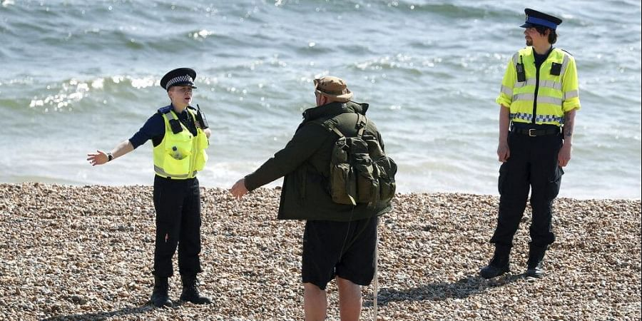 Police officers speak to a man as they patrol the beach in Brighton as the UK continues its lockdown to help curb the spread of coronavirus, in Brighton, England, Saturday April 25, 2020.