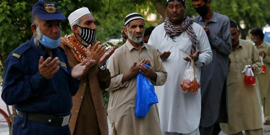 People pray before receiving free food for breaking their fast on the second day of Ramadan, in Islamabad, Pakistan. Sunday, April 26, 2020.