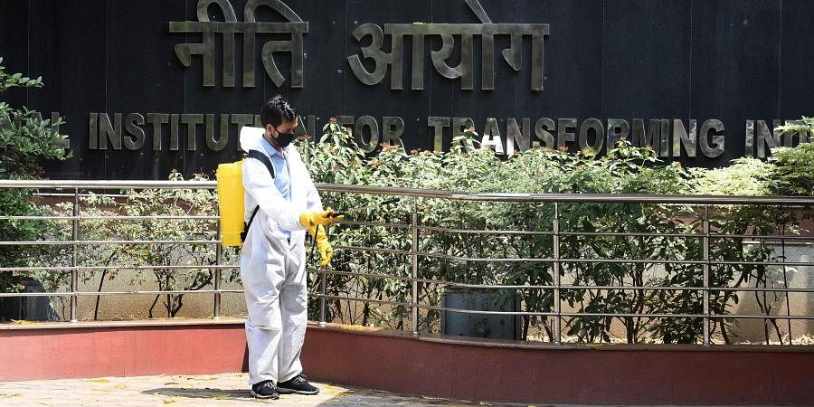 A health worker sanitises the premises of NITI Aayog building after a director level officer tested positive for COVID-19, during the nationwide lockdown to curb the spread of coronavirus, in New Delhi