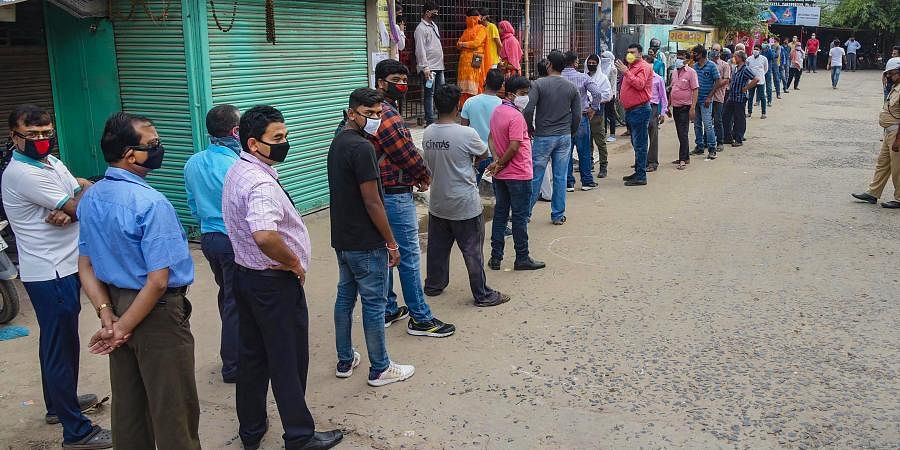 People queue-up outside at book shop to purchase stationery items during ongoing COVID-19 lockdown in Patna. (Photo | PTI)