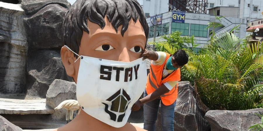 Statue of a boy with a mask 'Stay Home'  inside a theme based junction. (Photo| EPS/ RVK Rao)