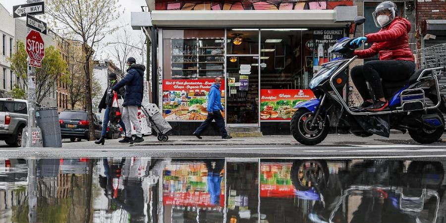 In this April 27, 2020, file photo, pedestrians and motorists wear personal protective equipment as they pass a small grocery that is one of the few businesses open on the street in New York.