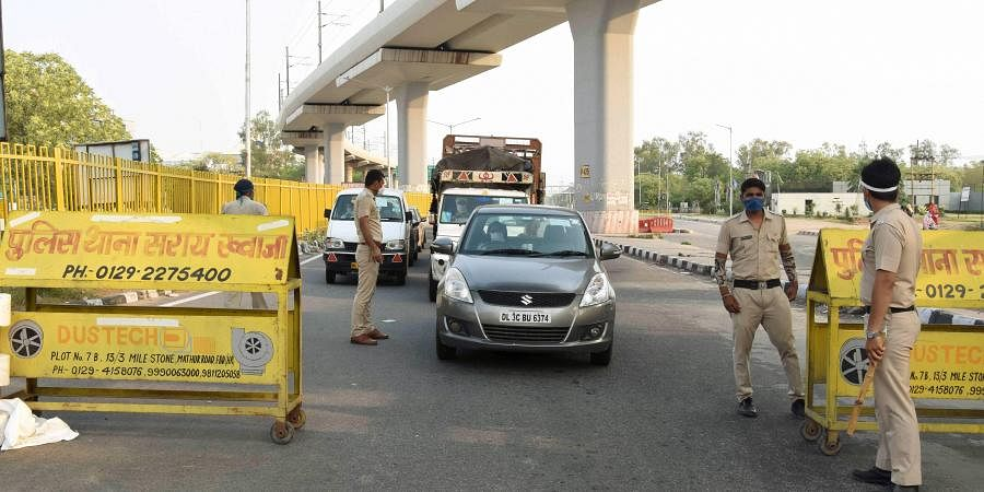 Police personnel stop commuters at Delhi-Faridabad border after all Haryana borders with Delhi were sealed during the nationwide in wake of the coronavirus pandemic in Faridabad