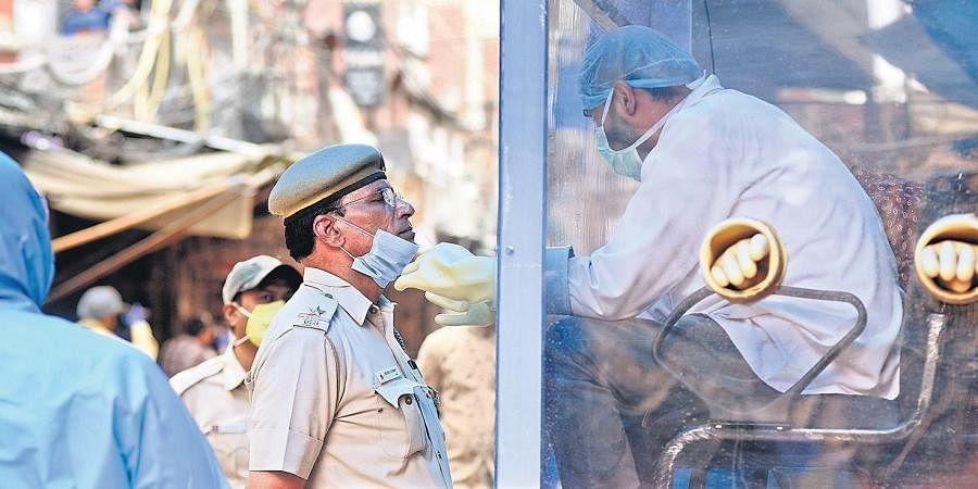 A health worker collects swab samples from a police personnel at a mobile COVID-19 testing centre in New Delhi on Monday