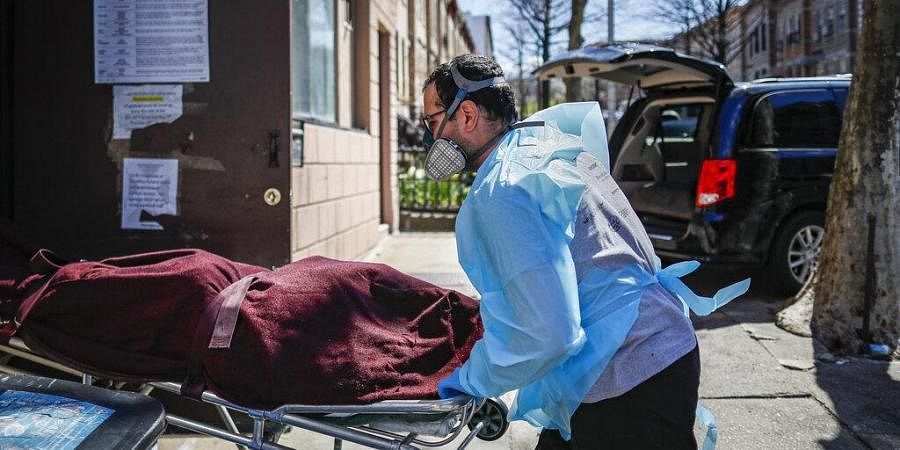 Employees deliver a body at Daniel J. Schaefer Funeral Home, Thursday, April 2, 2020, in the Brooklyn borough of New York.