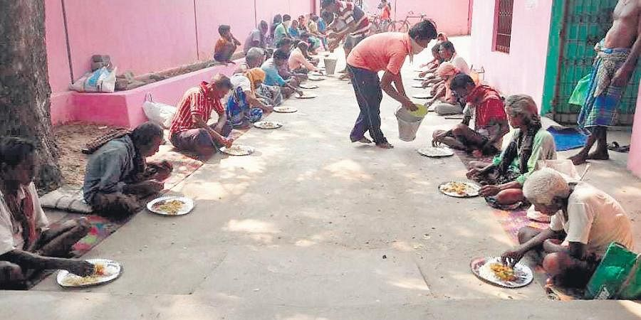 Cooked food being served on premises of a gram panchayat office in Mahanga