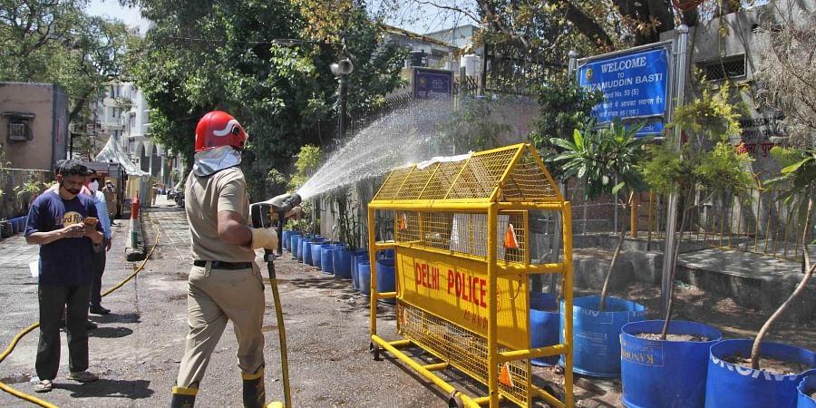 Delhi fire service staff sanitise area near the Nizamuddin mosque in New Delhi