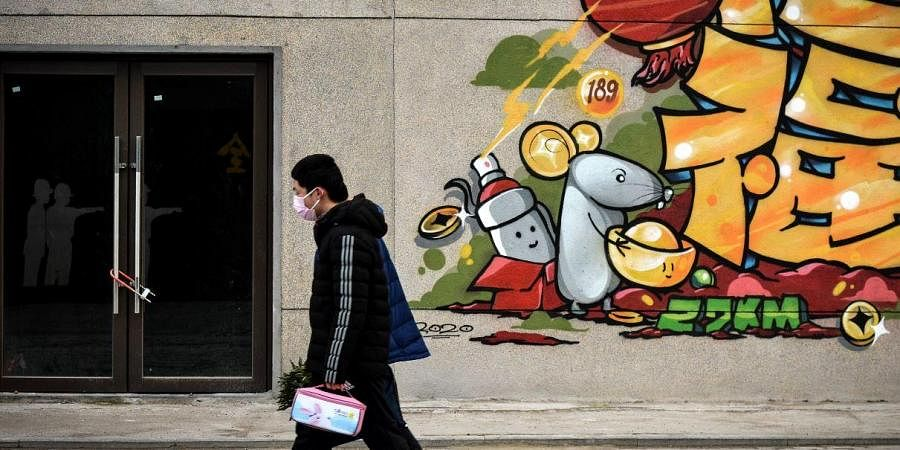 In this Saturday, Feb. 22, 2020, photo, a man wearing a protective face mask walks by a prosperity decoration on a closed building in Wuhan in central China's Hubei province.