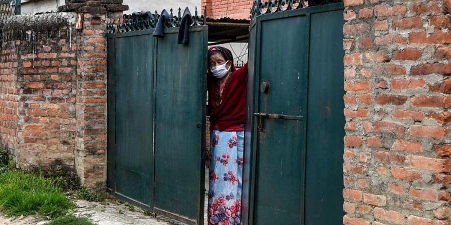 A woman stands at the gate of her home as she looks out on the empty street door in Kathmandu