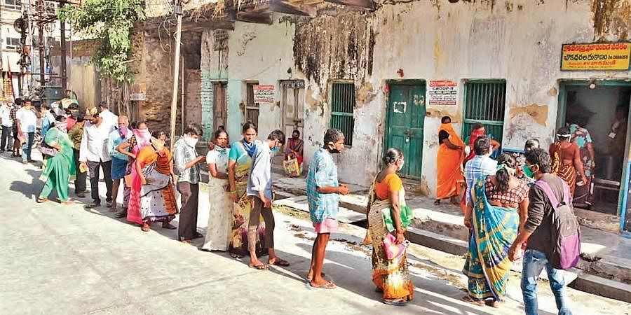 People waiting in a queue to collect ration in front of a fair price shop in Vijayawada on Wednesday