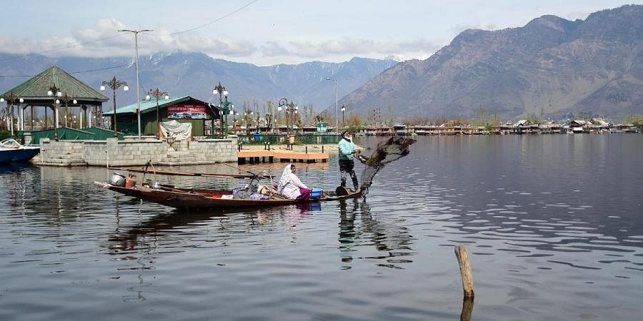 boatman casts his net into Dal lake during the nationwide lockdown amid COVID-19 pandemic, in Srinagar
