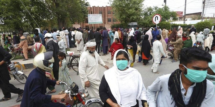 People wait to receive free food supplies provided by the local administration during a lockdown in Multan, Pakistan, Tuesday, March 31, 2020.
