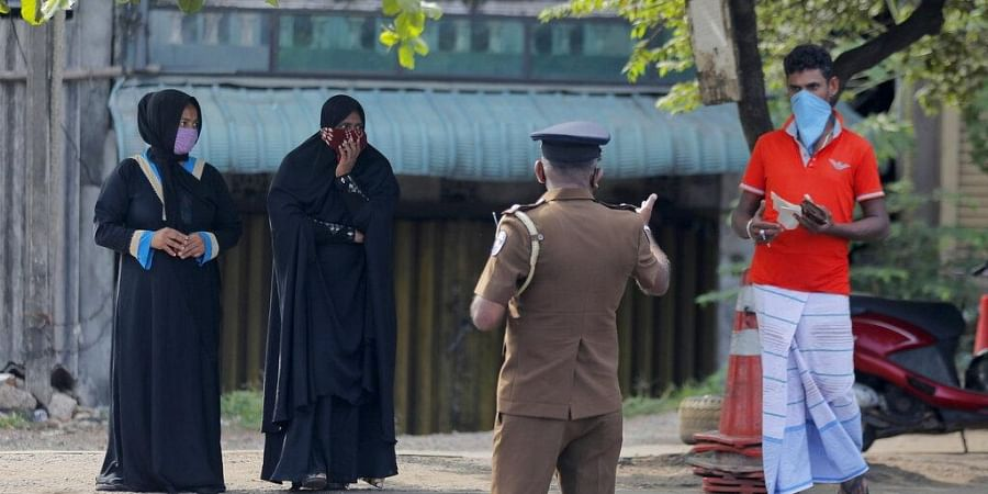A Sri Lankan police officer detains curfew violators during a curfew imposed to curb the spreading of new coronavirus in Colombo, Sri Lanka, Wednesday, April 1, 2020.