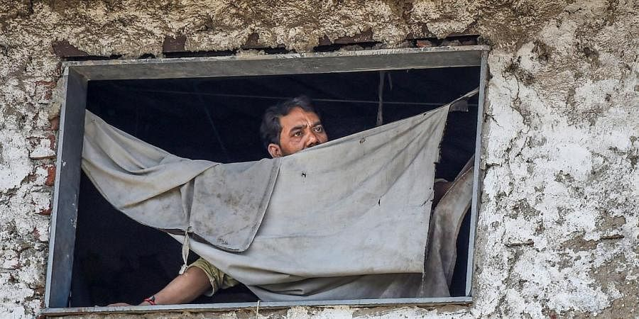 A man looks on through the window of his house during a nationwide lockdown in the wake of coronavirus pandemic at Dharavi in Mumbai