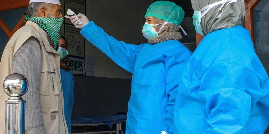 Doctors wearing protective gear scan visitors at the entrance of a hospital in wake of coronavirus outbreak, during the nationwide lockdown, in Srinagar
