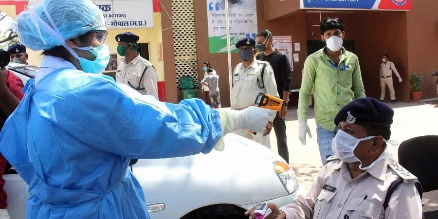 A doctor uses thermal screening on police personnel at Jahangirabad police station after security personnel tested positive for COVID-19, in Bhopal