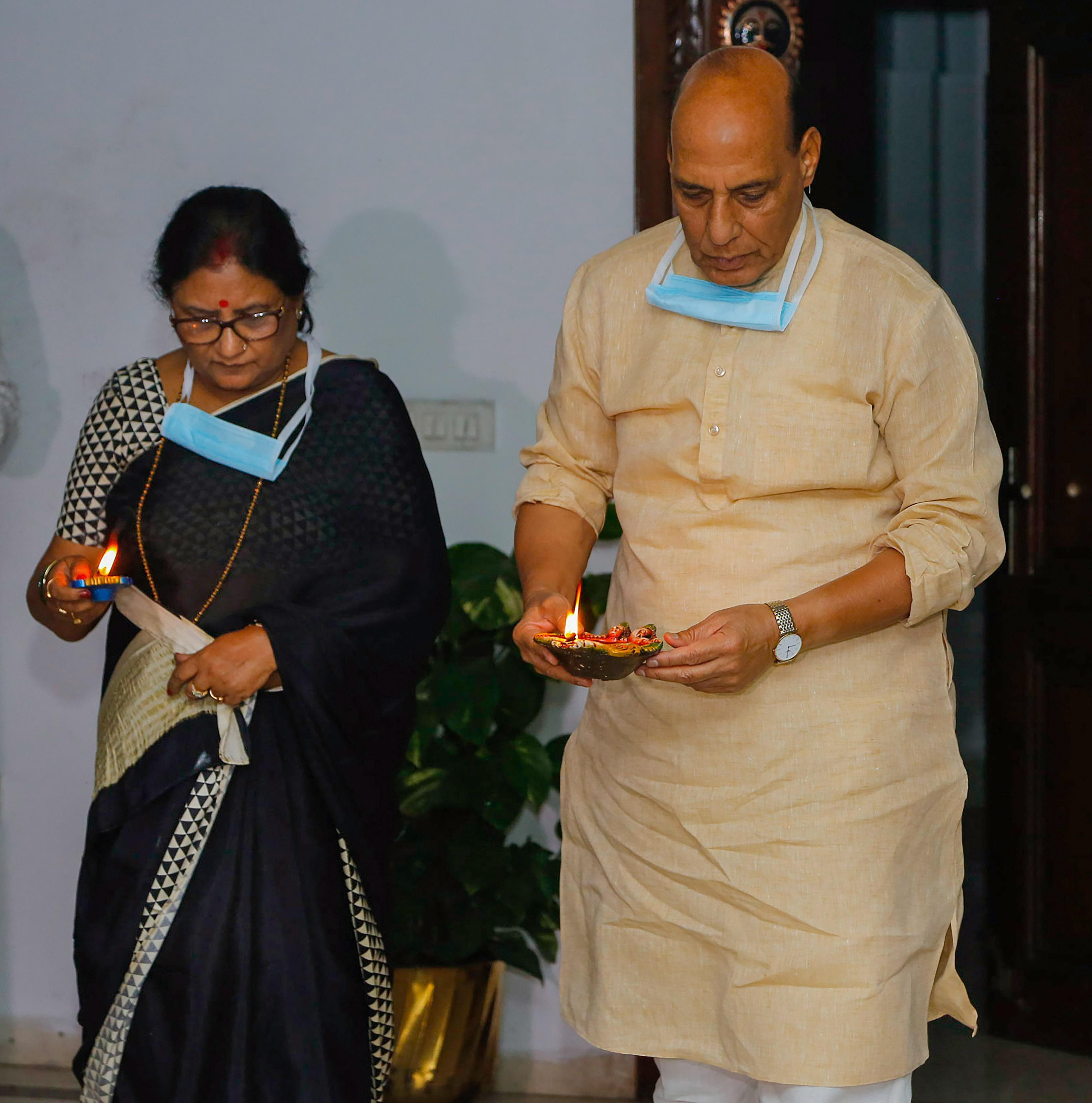 Defence Minister Rajnath Singh joins the nation in lighting lamps for nine minutes to express the country's unity in fight against COVID-19, amid the nationwide lockdown, in New Delhi, Sunday.