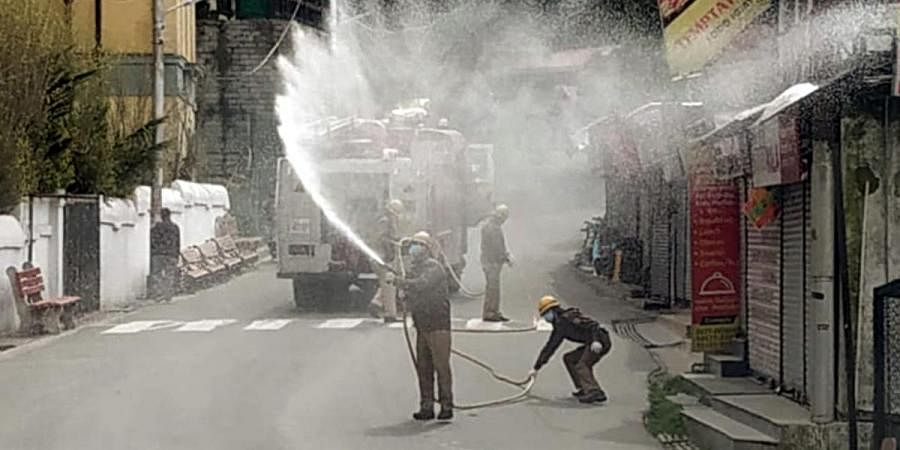 Municipal workers spraying disinfectant to contain the spread of coronavirus, in Shimla