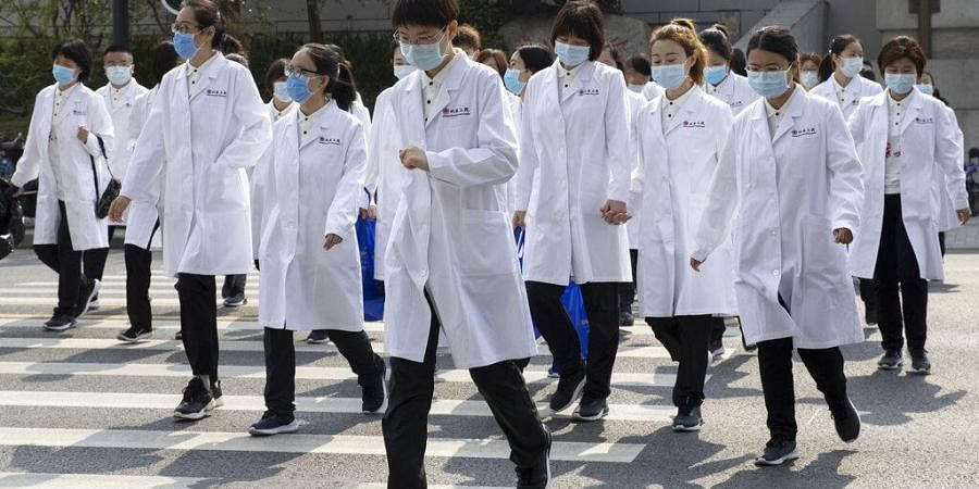 Medical workers from Beijing walk near a park during a day off as the city of Wuhan slowly loosens up ahead of a lifting of the two month long lockdown in central China's Hubei province on Sunday, April 5, 2020.