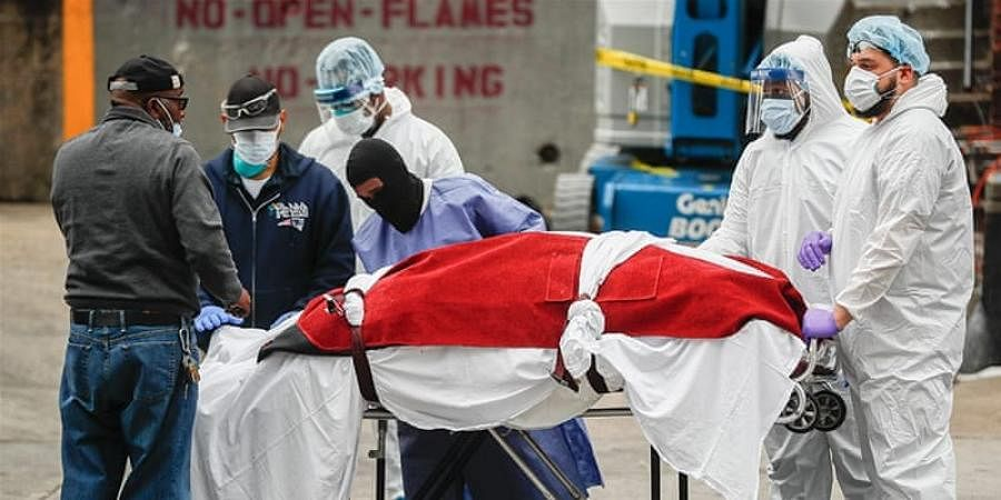 A body wrapped in plastic that was unloaded from a refrigerated truck is handled by medical workers wearing personal protective equipment at Brooklyn Hospital Center in New York City.