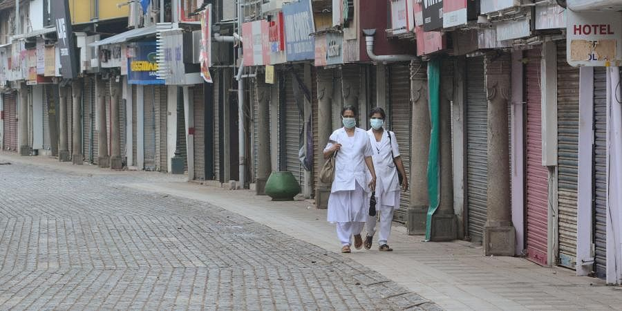 Two nurses walk down an empty SM Street to reach Kottapparambu Mother and Baby Hospital in Kozhikode during coronavirus lockdown.