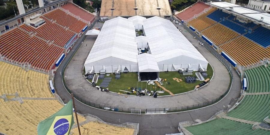 Workers set up a temporary field hospital to treat patients who have COVID-19 inside Pacaembu stadium in Sao Paulo, Brazil, Monday, March 30, 2020.