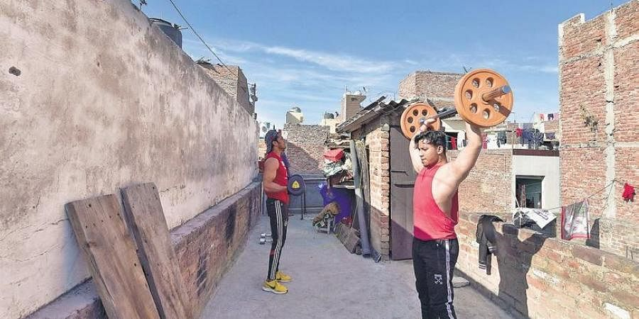 As gyms are shut, youngsters work out on the roof of their house during the nationwide lockdown at Shakur Basti in North West Delhi | FILE