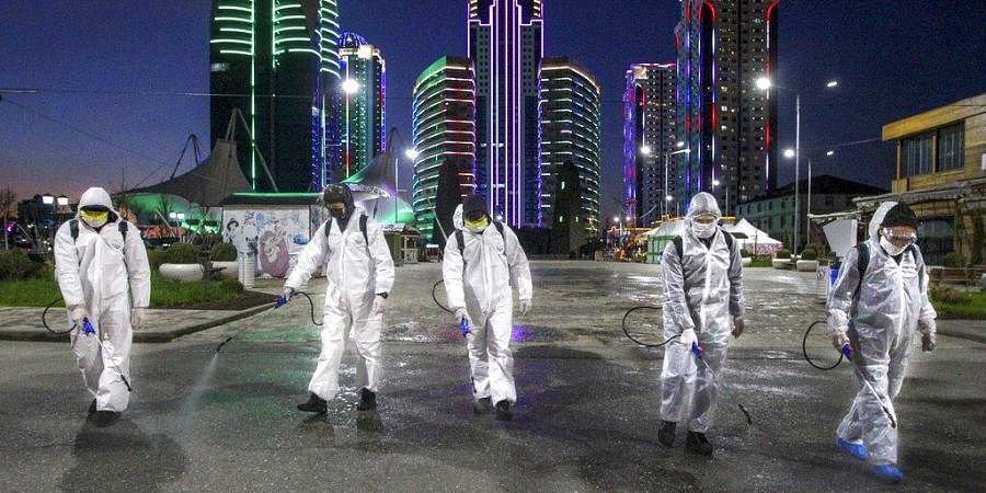 Municipal workers wearing protective suits spray disinfectant in an area in the center of Grozny, Russia, Monday, April 6, 2020.